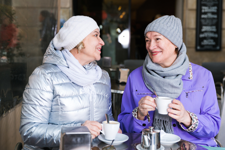 Smiling elderly females enjoying time together at cozy outdoor cafe in autumn day