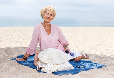 Positive mature woman resting on sand after beach walk Фото со стока