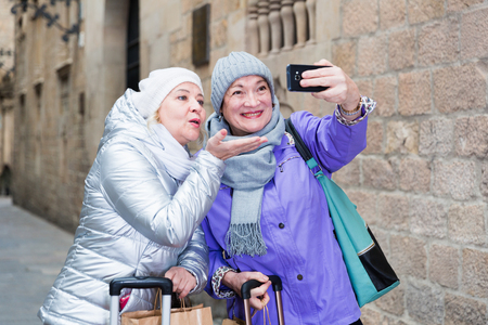 Two smiling senior ladies making selfie outdoors while traveling together