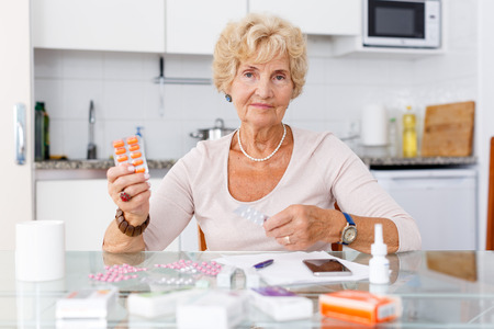 Portrait of attractive mature woman sitting among a lot of pills