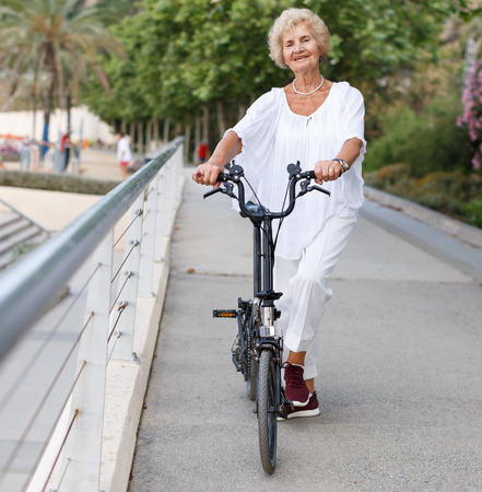 Portrait of casual senior woman going to bike at summer day Фото со стока - 111433882