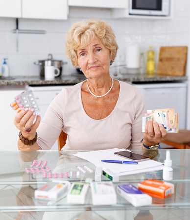 Elderly woman counting her expenditure on medicines sitting in kitchen Stock fotó