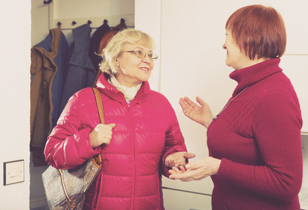 Positive old woman saying goodbye to friend female in jacket indoors Standard-Bild