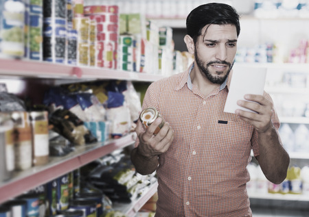 Adult man is choosing Oregano with help note list in market.
