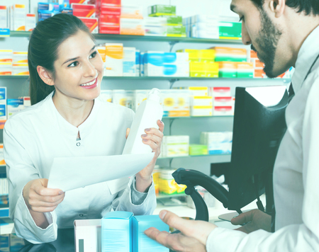 Diligent  cheerful smiling woman pharmacist is recommending medicine for man client in apothecary.