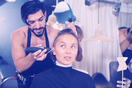 Cheerful male professional shaving females hair in hairdressing salon Imagens