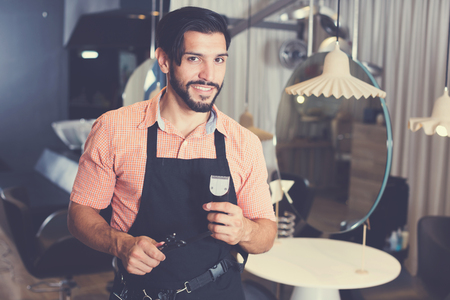 positive sexy worker man hairdresser standing in hairdressing studio Stock Photo