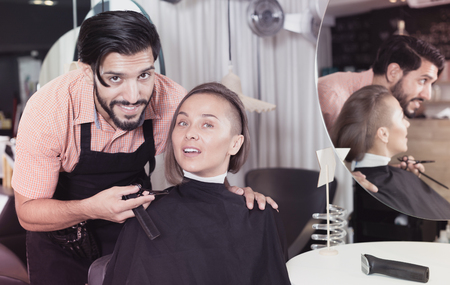 Portrait of young man hairdresser and female visitor in salon