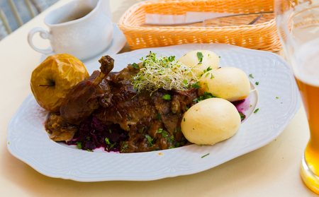 Delicious baked duck with blue cabbage and yeast dumplings decorated stewed apple and microgree