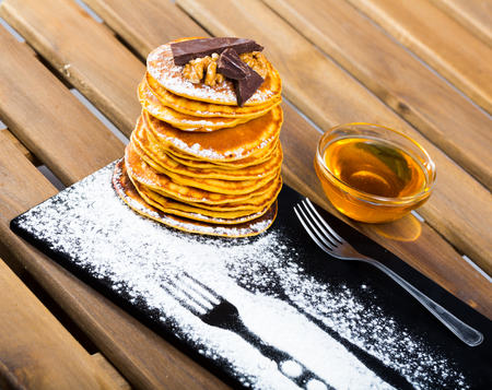 Stack of delicious pancakes on black plate with chocolate, walnuts and honey
