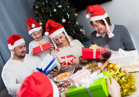 Portrait of cheerful family in Santa hats exchanging Christmas gifts at festive table