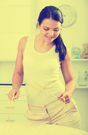 Young brunette woman measures waist by measuring tape