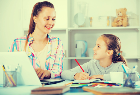 Smiling mother and daughter doing homework at the table at home