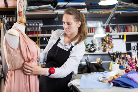 Woman  standing near dress at  mannequin at sewing workshop