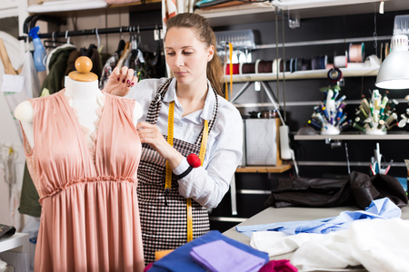 Serious woman professional measuring dress at  mannequin at sewing workshop Imagens