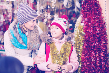 mother with happy little daughter buying decorations for Xmas at an open air market Stock Photo