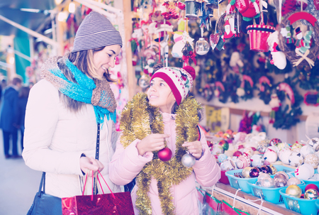young mother with little daughter buying decorations for Xmas at an open air market Stock Photo