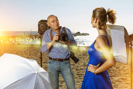 Professional photographer shooting young female model on seaside in sunny day