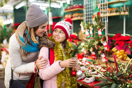 Glad mom and girl looking at flowers decoration at Christmas market Stock Photo - 111694937