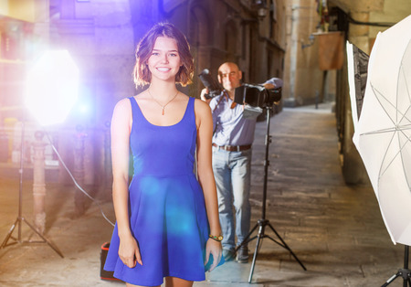 Portrait of young smiling girl on background with professional photographer during photo shoot on town street