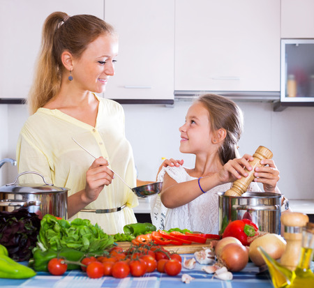 Smiling young mother and little daughter preparing vegetables in slow-cooker