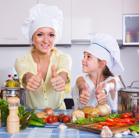 happy american mom and little daughter cooking vegeterian dish indoors
