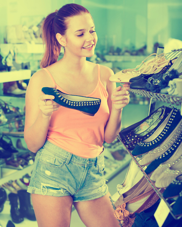 Cheerful smiling teenager girl choosing pair of shoes in boutique