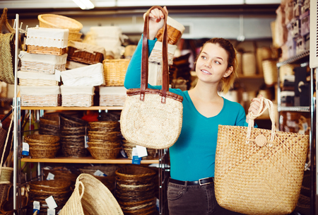 Young female customer standing with wicker bag in shop for decor