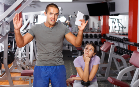 Sporty man and girl capturing on piece of paper training results at gym
