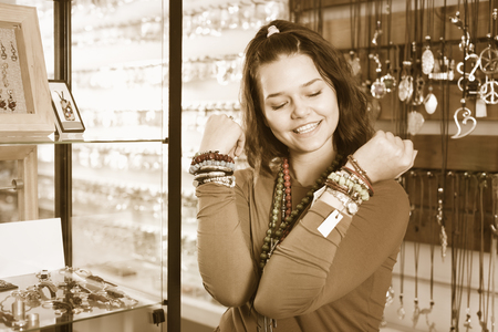 Cheerful young woman selling different pendants and bracelets in the market Reklamní fotografie