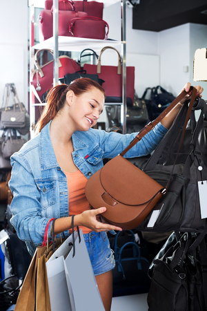 Cheerful teenager girl buying handbag in fashion shop Banque d'images