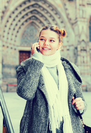 portrait of girl teenager talking on phone in scarf and coat