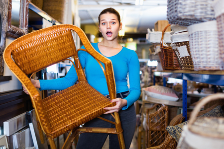 Happy positive young customer woman standing with wicker chair in shop for decor