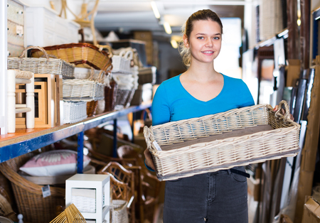 Young girl customer standing with wicker basket in shop for decor Archivio Fotografico