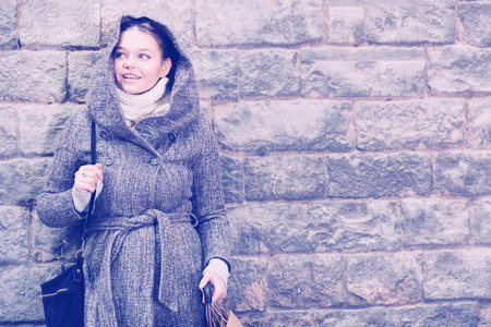 cheerful female in the historical city in coat hood near wall