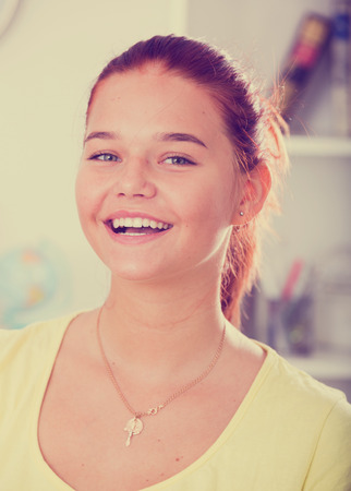 closeup portrait of smiling teenager girl indoors in light interior