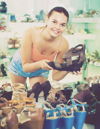 portrait of smiling young girl looking after pair of shoes in fashion store Stock Photo