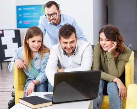 Young happy cheerful  people friendly discussing while sitting with laptop in common hall of hostel Stock Photo