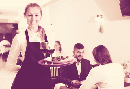 Affable female waiter is standing with order in luxury restaurante indoor.