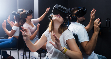Young girls and guys making gestures when wearing virtual reality headset together indoors Banque d'images