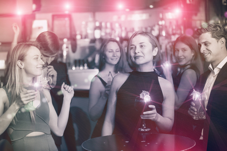 Cheerful colleagues dancing on corporate party with cocktails in hands Stock Photo