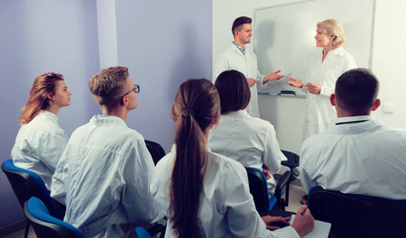 Young guy medical student communicating with teacher in front of group of students in auditorium