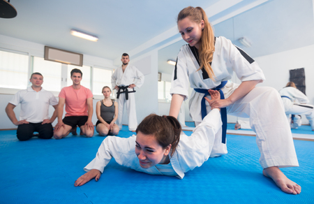 Females are training in pair to use taekwondo technique during class.