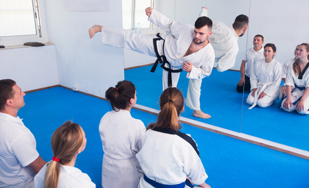 Young male coach demonstrating new techniques to adults in karate class