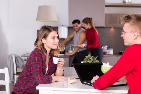 Positive girl friendly discussing with guy who sitting with laptop in common kitchen of hostel Banque d'images