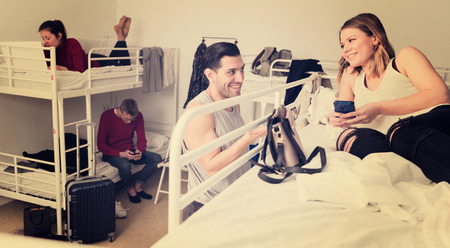 Smiling Hispanic traveler friendly talking to attractive girl during rest in hostel bedroom