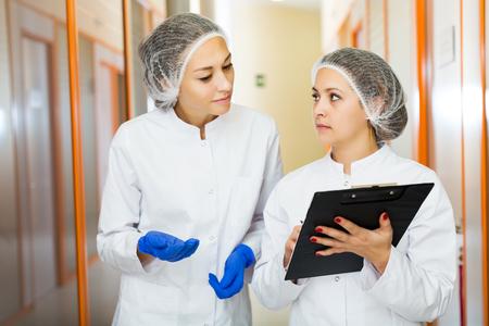 Young female doctors describing beauty procedures in aesthetic medicine center Standard-Bild