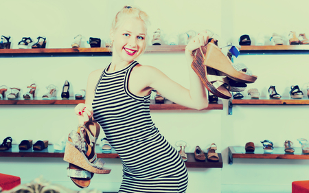 Positive  beautiful  woman standing in boutique and having many shoes in hands