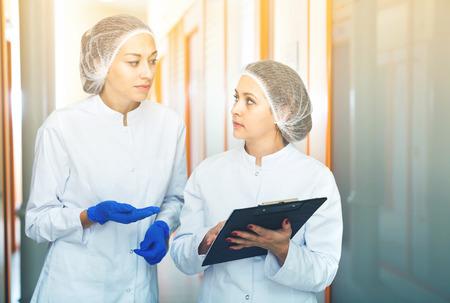 Diligent friendly  female doctors discussing beauty procedures in aesthetic medicine center Standard-Bild - 111779711