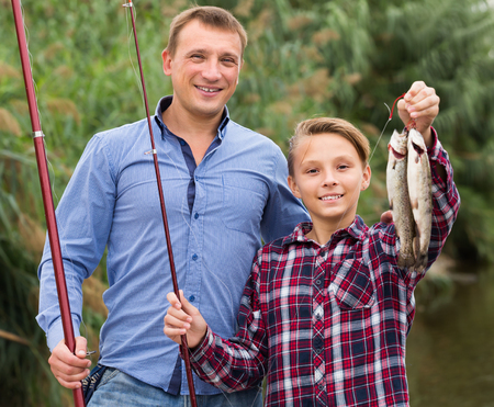Portrait of glad father with teenager son looking at fish on hook in hands outdoors 版權商用圖片